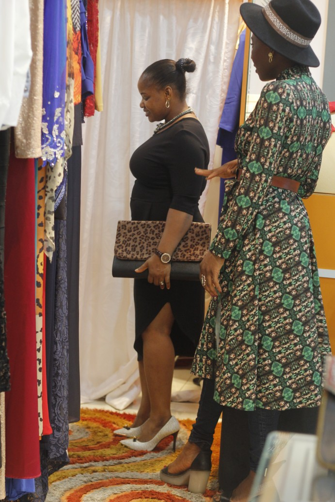 Immaculate tries on some clothes at the Mobos Fashion store.